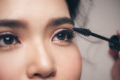 Close-up portrait of beautiful girl touching black mascara to he stock image
