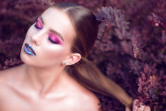 Close up portrait of beautiful glam model with perfect bright fashion make up posing with closed eyes in barberry bushes stock photos