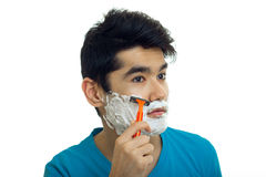 Close-up portrait of a beautiful guy with foam on his face who shaves his beard Stock Photos