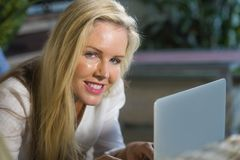 Close up portrait beautiful and happy blond woman 40s relaxed at home using internet on laptop working lying comfortable on sofa a. Close up portrait beautiful Stock Images