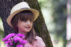 Close up portrait of a beautiful little girl with big blue eyes,. With a hat while holding a bouquet of flowers. She is waiting for someone and wants to Royalty Free Stock Image