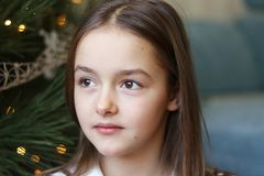 Close up portrait of beautiful little girl with brown eyes sitting under Christmas tree daydreaming stock photography