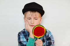 Close up portrait of beautiful little male child in cap and shirt holding huge lollipop in one hand and looking at it with serious Royalty Free Stock Images