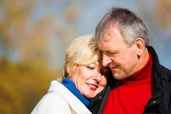 Retired senior couple embracing in park stock images