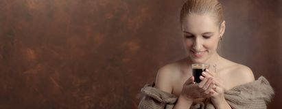 Close-up portrait of a beautiful mid age woman with cup of coffee. Attractive and happy blonde in sweater with bare shoulders drinks coffee. Copy space stock photos