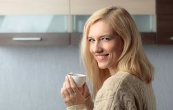 Close-up portrait of a beautiful mid age woman with cup of coffee. Attractive and happy blonde in sweater drinks coffee. Copy space stock photography