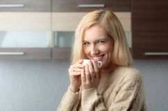 Close-up portrait of a beautiful mid age woman with cup of coffee. Attractive and happy blonde in sweater drinks coffee. Copy space stock photos