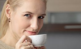 Close-up portrait of a beautiful mid age woman with cup of coffee. Attractive and happy blonde in sweater drinks coffee. Copy space royalty free stock images