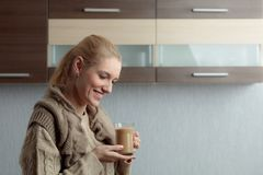 Close-up portrait of a beautiful mid age woman with cup of coffee. Attractive and happy blonde in sweater drinks latte. Copy space royalty free stock photo