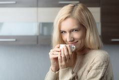 Close-up portrait of a beautiful mid age woman with cup of coffee. Attractive and happy blonde in sweater drinks coffee. Copy space royalty free stock photos