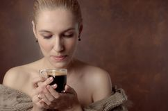 Close-up portrait of a beautiful mid age woman with cup of coffee. Attractive and happy blonde in sweater with bare shoulders drinks coffee. Copy space stock image