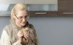 Close-up portrait of a beautiful mid age woman in glasses with cup of coffee. Attractive and happy blonde in sweater drinks latte. Copy space stock photo