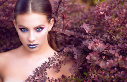 Close up portrait of beautiful model with perfect bright fashion make up and penetrating glance posing in barberry bushes royalty free stock images