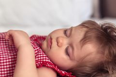 Close up portrait of a beautiful nine month old baby girl sleeping on blurred background. Sleeping child face. Cute stock photos