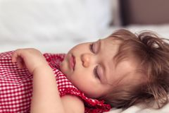 Close up portrait of a beautiful nine month old baby girl sleeping on blurred background. Sleeping child face. Cute royalty free stock photo