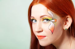 Close-up portrait of beautiful red-haired girl with flower painted on his face Stock Photos