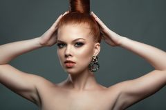 Close up portrait of beautiful red-haired model with her hair scraped back into a high bun holding her hands up touching it. Perfect make-up concept. Isolated royalty free stock images