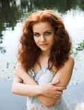 Near the lake. Close-up portrait of a beautiful red-headed girl posing near the lake stock image