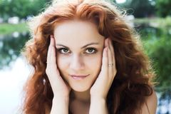 Red-headed nymph of the lake. Close-up portrait of a beautiful red-headed girl posing near the lake royalty free stock photography