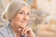 Portrait of beautiful senior woman smiling at home stock photos