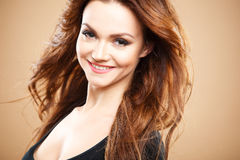 Close-up portrait of beautiful sexy young woman with long brown hair over brown background Royalty Free Stock Photos