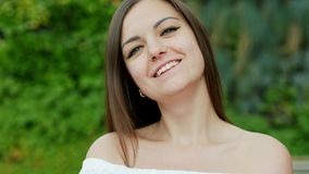 Close-up portrait of beautiful shy woman smiles to the camera on the street stock video footage