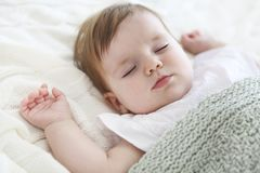Portrait of a beautiful sleeping baby on white. Close up portrait of a beautiful sleeping baby on white Royalty Free Stock Image