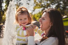 Close up portrait of beautiful small baby, blond little girl in colourful pullover in mothers hands in park outdoors Stock Photos