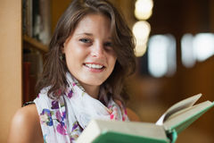 Close up portrait of a beautiful smiling female holding a book Royalty Free Stock Image