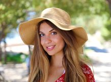 Close up portrait of a beautiful smiling girl with brown hair wearing a hat and looking at camera outdoors royalty free stock photography