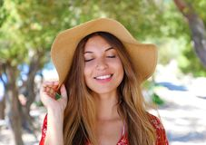 Close up portrait of a beautiful smiling girl with closed eyes wearing a hat and red dress outdoors stock image