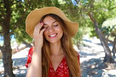 Close up portrait of a beautiful smiling girl with closed eyes wearing red dress and hat outdoors stock photos