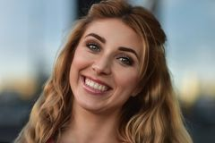 Close up portrait of a beautiful smiling girl with nice teeth outdoors at street. royalty free stock image