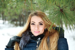Close-up portrait of beautiful smiling girl in winter pinewood Stock Image
