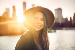 Close-up portrait of beautiful smiling woman looking to the side on the beach in city. Stock Photos