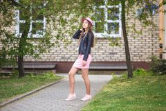Close up portrait of beautiful stylish kid girl in hat near brick building in urban street as background.  stock photography
