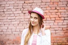 Close up portrait of beautiful stylish kid girl in hat near pink brick wall as background stock photos
