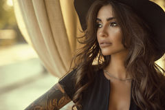 Close up portrait of beautiful tanned glam tattooed model with long wavy hair wearing black dress and wide brimmed hat. Looking aside, sandy yellow curtains on royalty free stock images