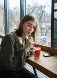 Close up portrait of beautiful teen student girl with a glass mug drinks through a straw fruit tea at street cafe sitting near big Stock Images