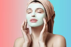 Close-up portrait of a beautiful and well-groomed woman in a towel and with a mask on her face on a multicolored background. Face. And body care. Spa, beauty Royalty Free Stock Photo