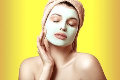 Close-up portrait of a beautiful and well-groomed woman in a towel and with a mask on her face on a multicolored background. Face. And body care. Spa, beauty Royalty Free Stock Photography