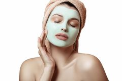 Close-up portrait of a beautiful and well-groomed woman in a towel and with a mask on her face on a white background, isolated. Fa. Ce and body care. Spa, beauty Stock Images
