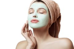 Close-up portrait of a beautiful and well-groomed woman in a towel and with a mask on her face on a white background, isolated. Fa. Ce and body care. Spa, beauty Stock Photography