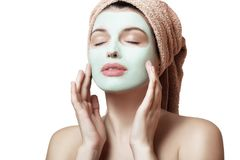 Close-up portrait of a beautiful and well-groomed woman in a towel and with a mask on her face on a white background, isolated. Fa. Ce and body care. Spa, beauty Stock Image