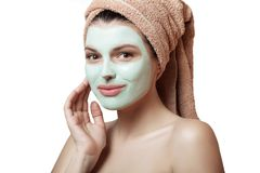 Close-up portrait of a beautiful and well-groomed woman in a towel and with a mask on her face on a white background, isolated. Fa. Ce and body care. Spa, beauty Royalty Free Stock Photography