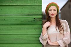 Close Up Portrait of a Beautiful Woman. Leaning against a green wooden wall outdoors. Possible for copy space Royalty Free Stock Images