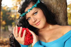 Close-up portrait of beautiful woman in blue. With red arrow-wood, outdoors stock images