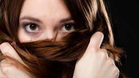 Closeup woman covers the face by long brown hairs Stock Photography