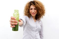 Beautiful woman with curly hair holding bottle of green juice Royalty Free Stock Photography