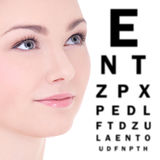 Close up portrait of beautiful woman and eye test chart isolated. On white background Royalty Free Stock Images